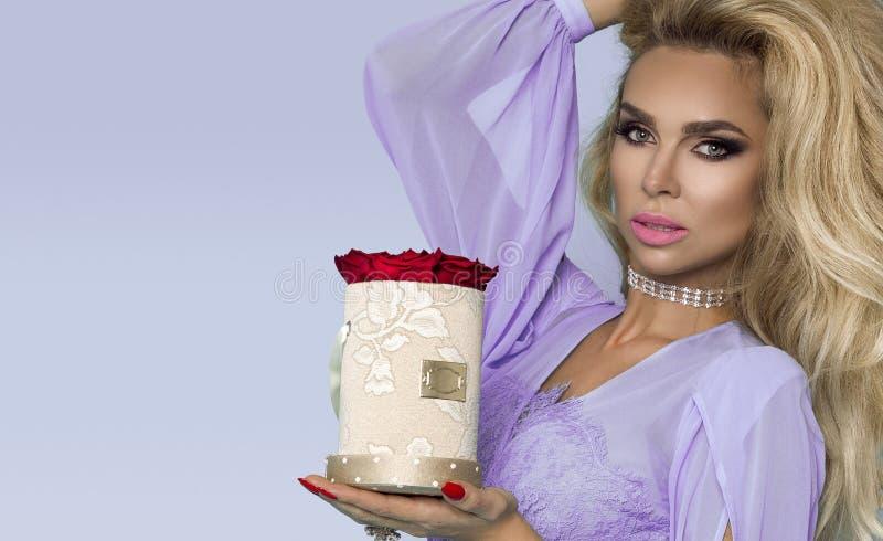 Красивая белокурая модель в элегантном платье держа букет роз, коробку цветка Валентайн и подарок на день рождения на голубой пре стоковые изображения