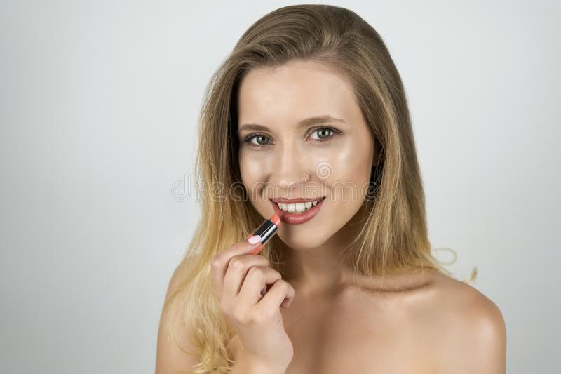 Красивая белокурая молодая усмехаясь женщина кладя губную помаду на конец вверх по изолированной белой предпосылке стоковые фото