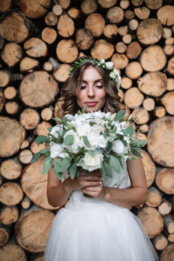 Красивая белокурая счастливая невеста в элегантном белом платье в венке с букетом outdoors стоковая фотография rf