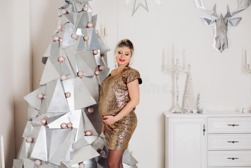 Красивая беременная женщина в сверкная платье партии на искусственной современной рождественской елке стоковая фотография