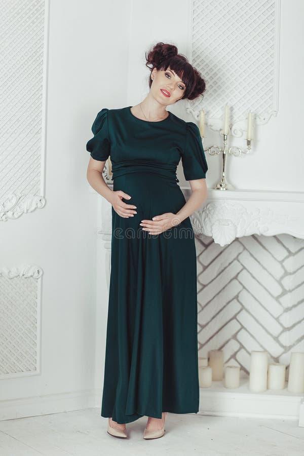 Красивая беременная женщина в черном платье на предпосылке камина с свечами в белой комнате стоковые фото