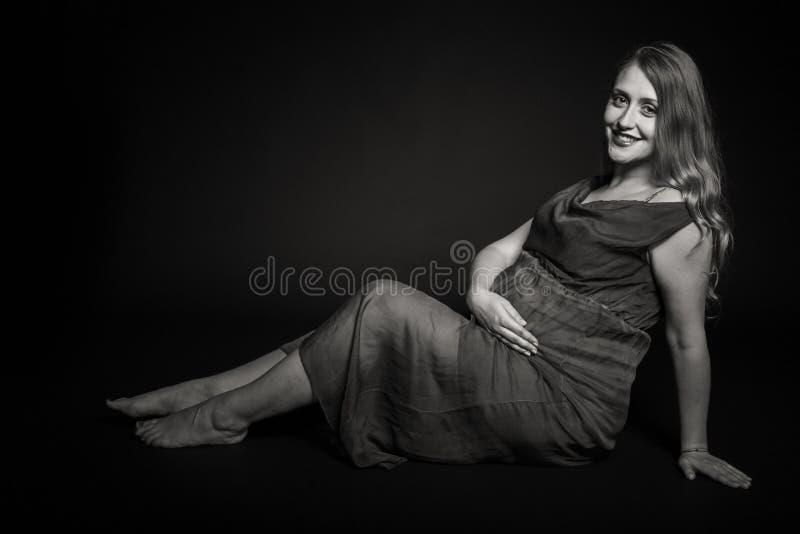 Красивая беременная женщина на темной предпосылке стоковое изображение rf