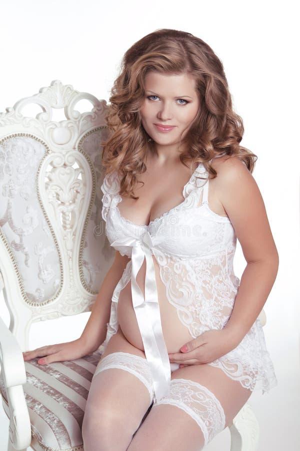 Красивая беременная женщина ослабляя на стуле изолированном на белизне стоковое изображение rf