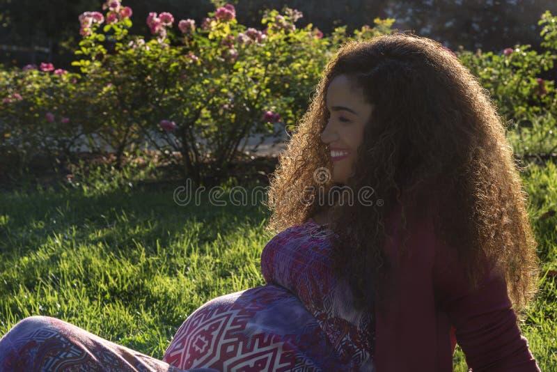 Красивая беременная женщина сидя в парке стоковая фотография