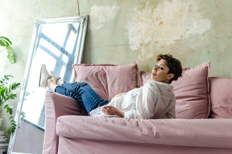 Красивая беременная женщина сидя на софе дома стоковые фото
