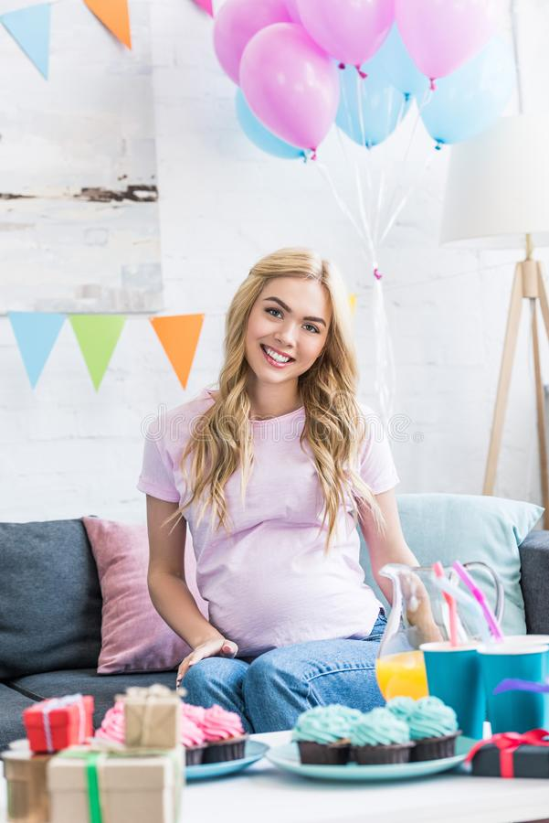 красивая беременная женщина сидя на софе и смотря камеру стоковое изображение