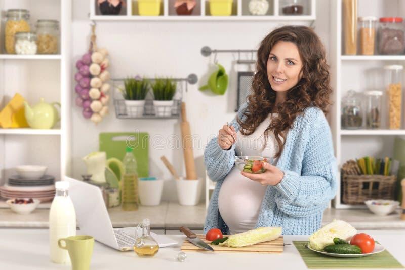 Красивая беременная женщина с едой стоковые изображения