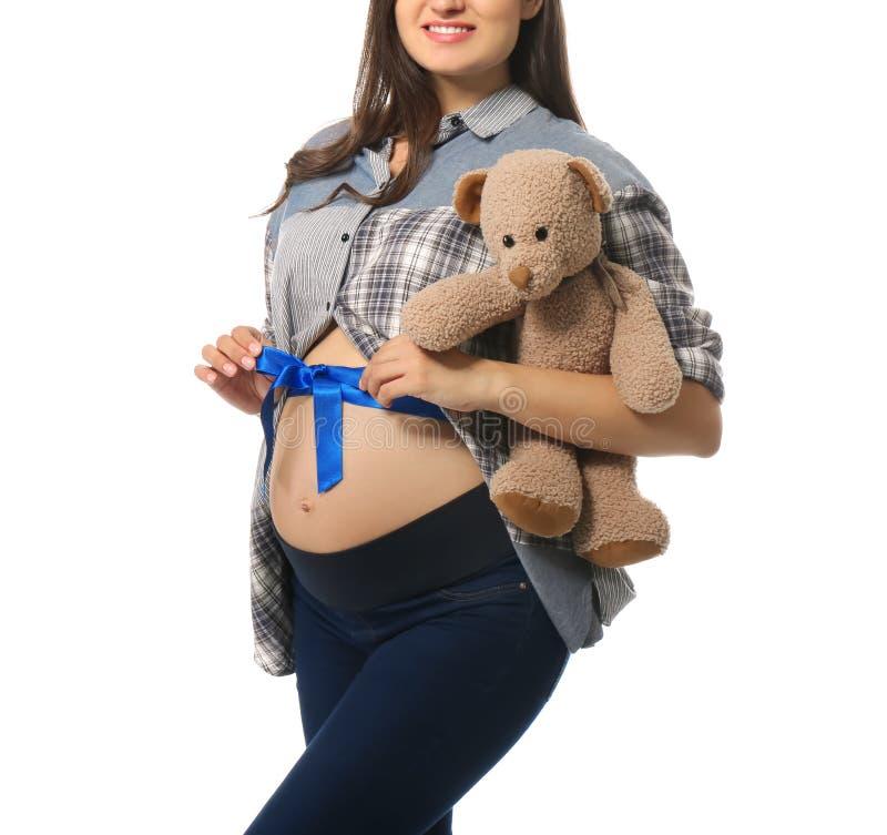 Красивая беременная женщина с медведем игрушки и голубая лента на ее животе против белой предпосылки стоковые изображения rf