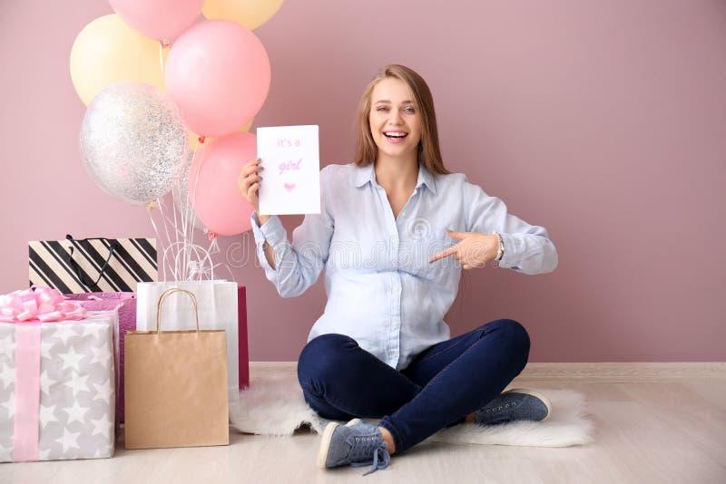Красивая беременная женщина с подарками детского душа около стены цвета стоковые изображения