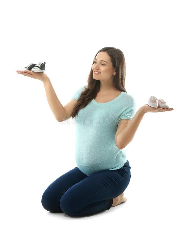 Красивая беременная женщина с girlish и мальчишескими добычами на белой предпосылке стоковая фотография