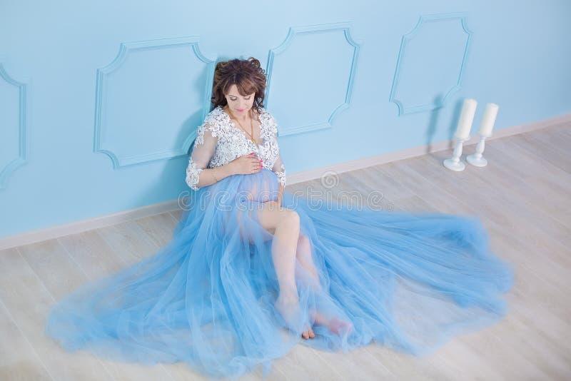 Красивая беременная молодая женщина нося роскошное голубое платье женского белья, портрет студии изумляя дамы с курчавыми волосам стоковая фотография