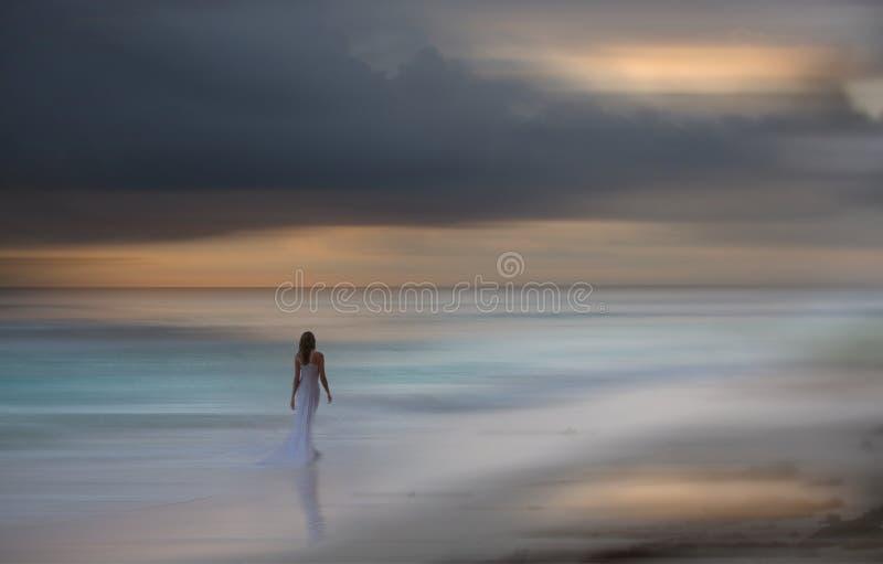 Красивая белизна одела прогулки женщины на пляже запачканная предпосылка стоковое изображение
