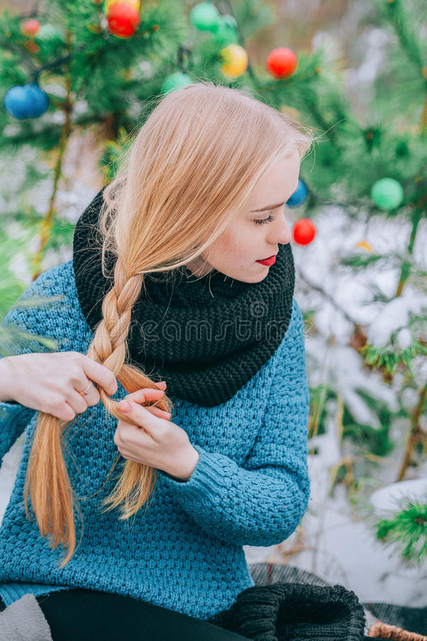 Красивая белокурая девушка заплетает оплетку, связанный свитер, день зимы волшебный, фото влияния ретро, зерно стоковое изображение rf