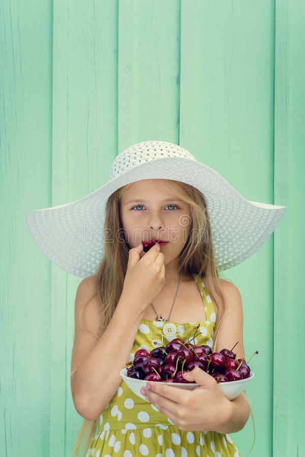 Красивая белокурая девушка на предпосылке стены бирюзы в белой шляпе держа плиту с вишней стоковое изображение rf