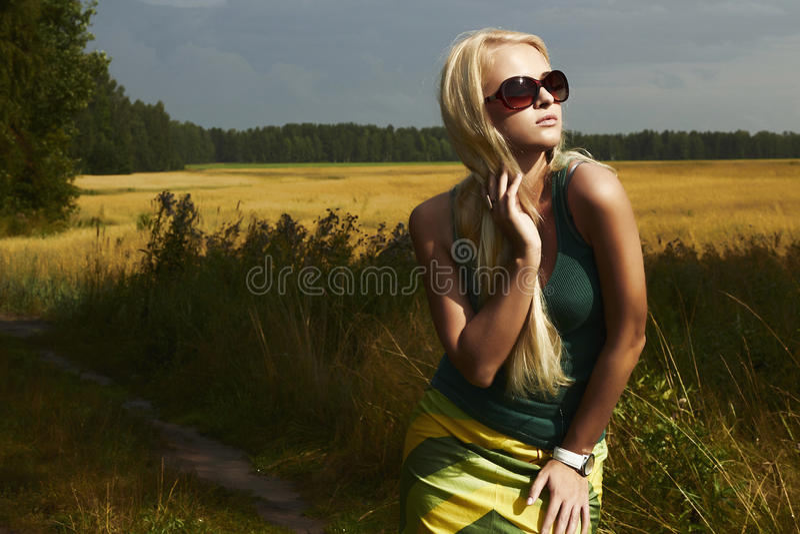 Красивая белокурая девушка на field.beauty woman.sunglasses стоковая фотография