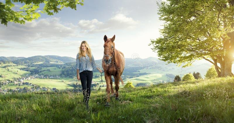 Красивая белокурая девушка с лошадью в чудесных ландшафтах стоковое изображение rf