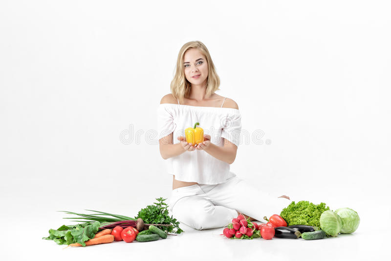 Красивая белокурая женщина в белых одеждах и сериях свежих овощей на белой предпосылке Девушка держит болгарский перец стоковые фото