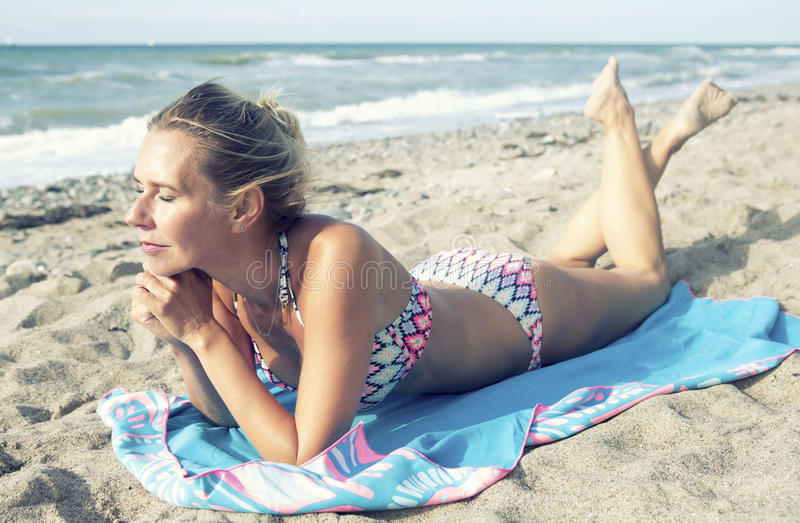 Красивая белокурая женщина в бикини лежа на пляже стоковое изображение rf