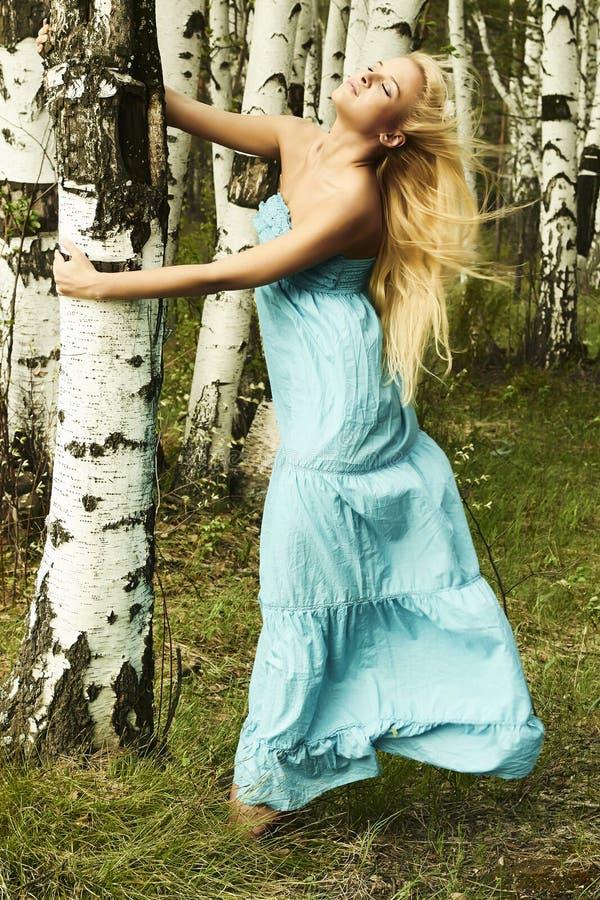 Красивая белокурая женщина в лесе. волосы летания стоковое изображение