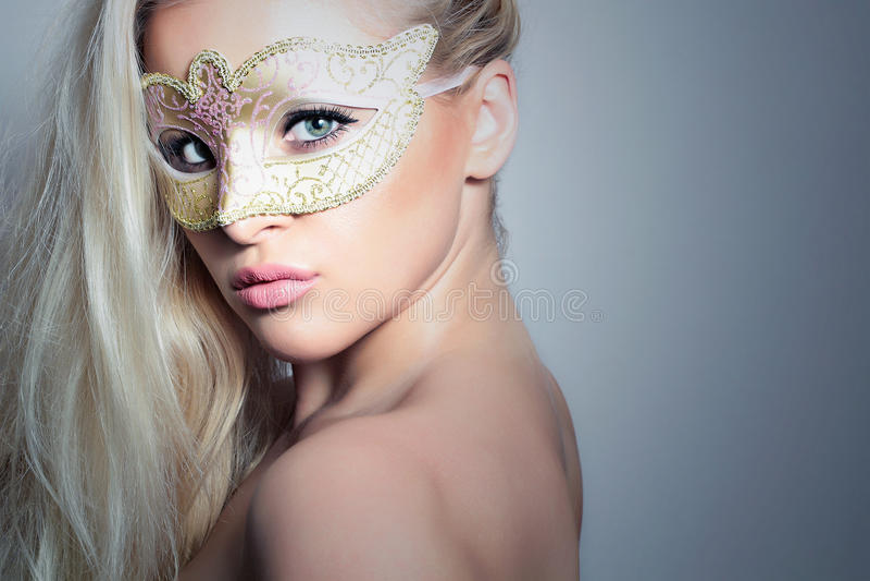 Красивая белокурая женщина в золотом Mask.Masquerade. Сексуальная девушка стоковые фото