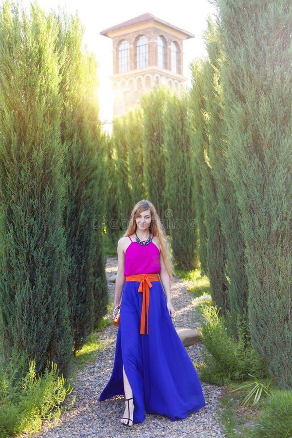 Красивая белокурая женщина в длинном красочном платье outdoors стоковое изображение rf