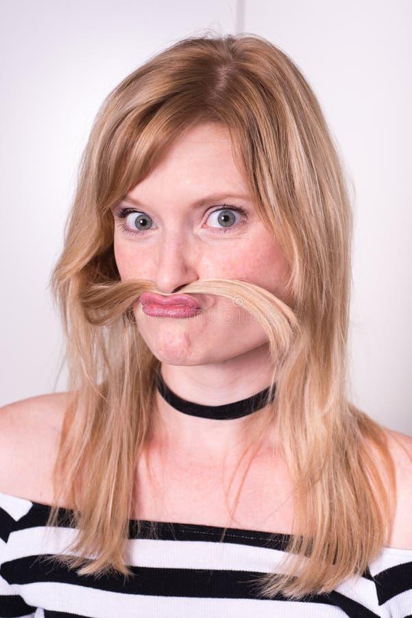 Красивая белокурая женщина делает усик с ее волосами стоковое изображение rf