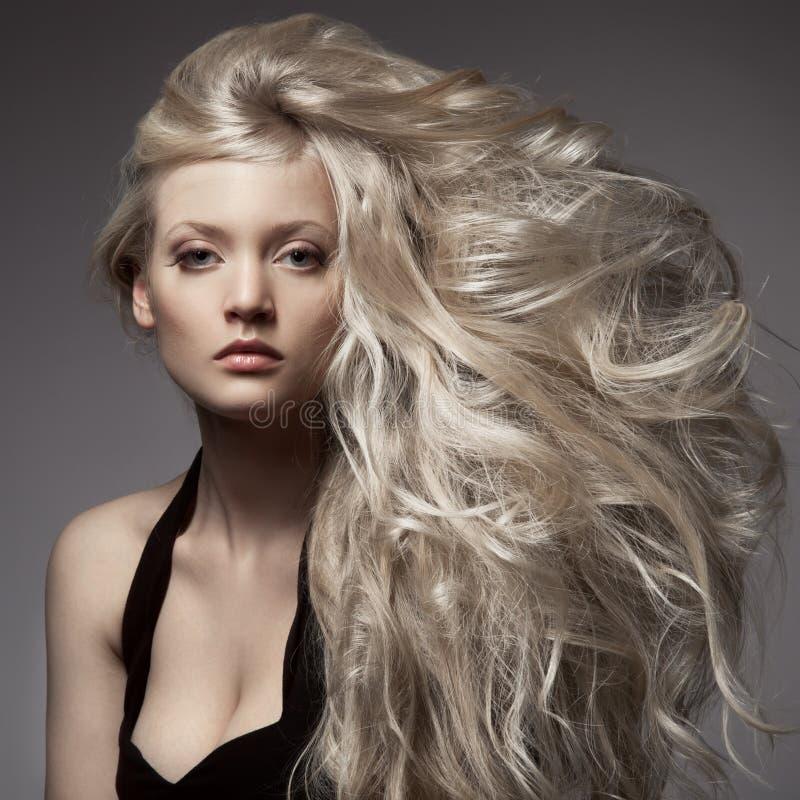 Красивая белокурая женщина. Курчавые длинные волосы стоковые фотографии rf