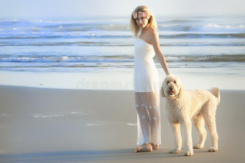 Красивая белокурая женщина на пляже в белом платье с ее собакой Goldendoodle стоковые изображения rf