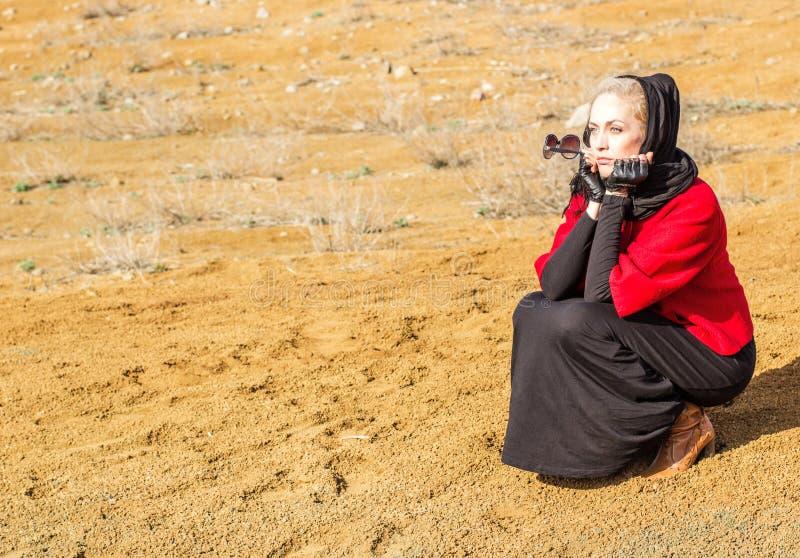 Красивая белокурая женщина сидя на песке стоковое фото rf