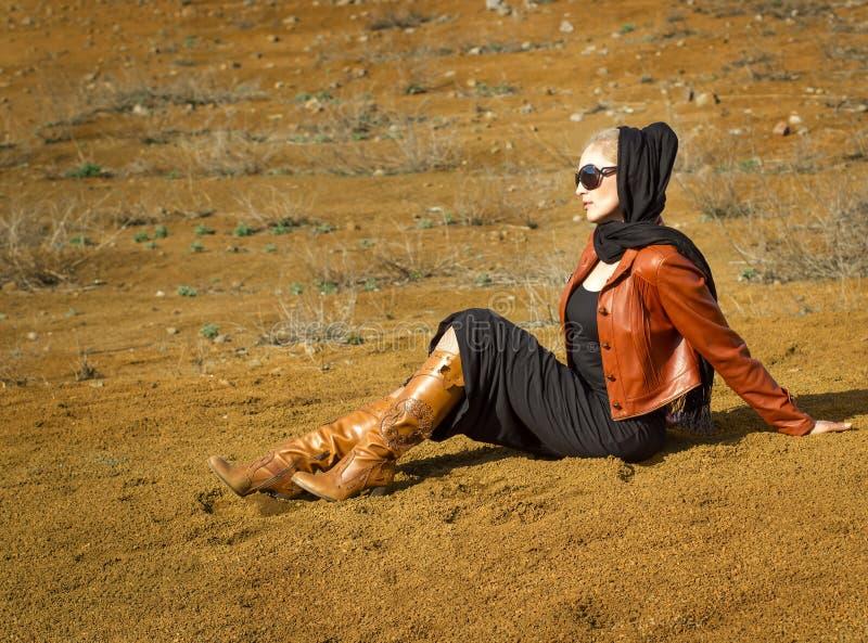 Красивая белокурая женщина сидя на песке стоковые фотографии rf