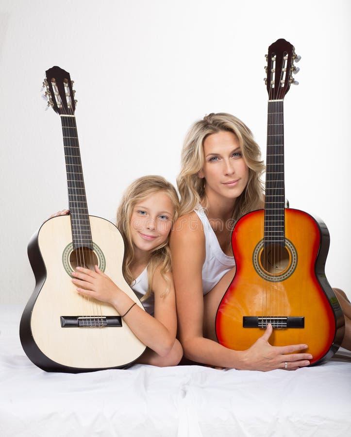 Красивая белокурая мать и ее дочь с гитарами стоковое изображение