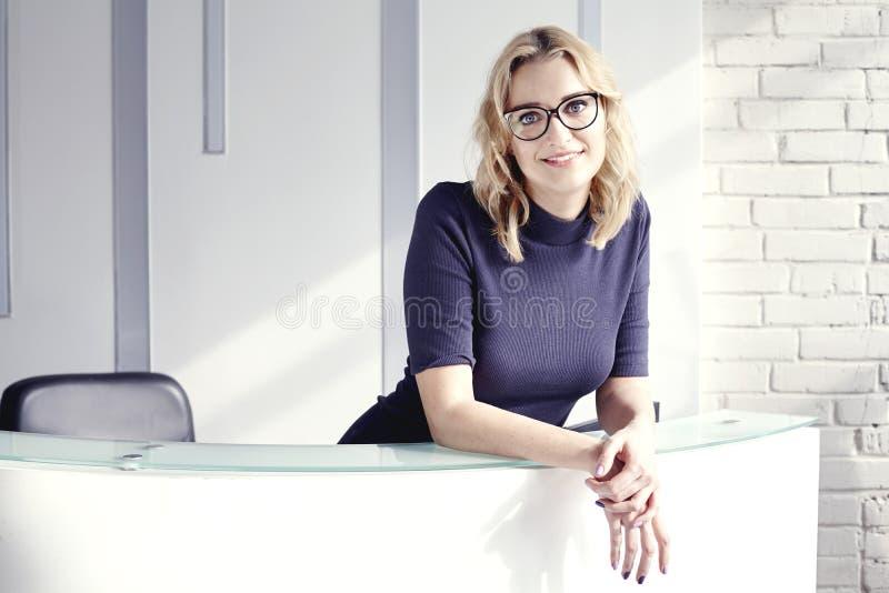Красивая белокурая дружелюбная женщина за приемной, встречей и усмехаться Солнечность в современном офисе стоковое изображение