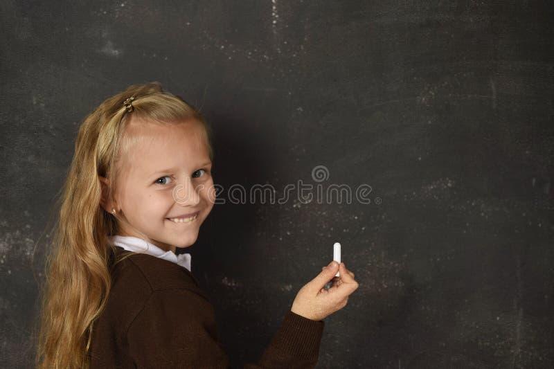 Красивая белокурая сладостная школьница в форме держа сочинительство мела на усмехаться классн классного счастливый стоковые фотографии rf