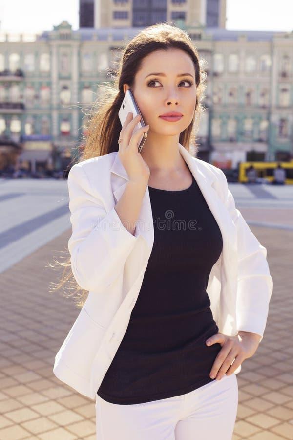Красивая бизнес-леди брюнет в белом костюме и черном t-shir стоковое изображение rf