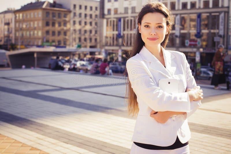 Красивая бизнес-леди брюнет в белом костюме с таблеткой в ее руках outdoors стоковые фото
