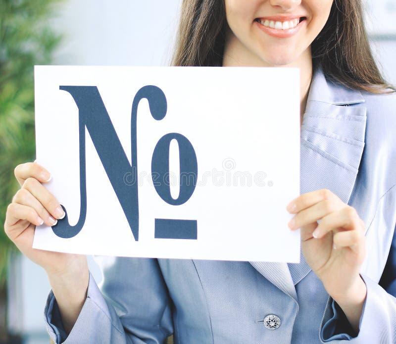 Красивая бизнес-леди в офисе держа знак с знаком числа стоковое изображение