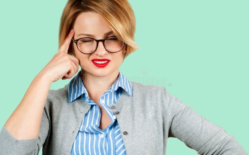 Красивая бизнес-леди думая ее планов на зеленой предпосылке стоковые фото