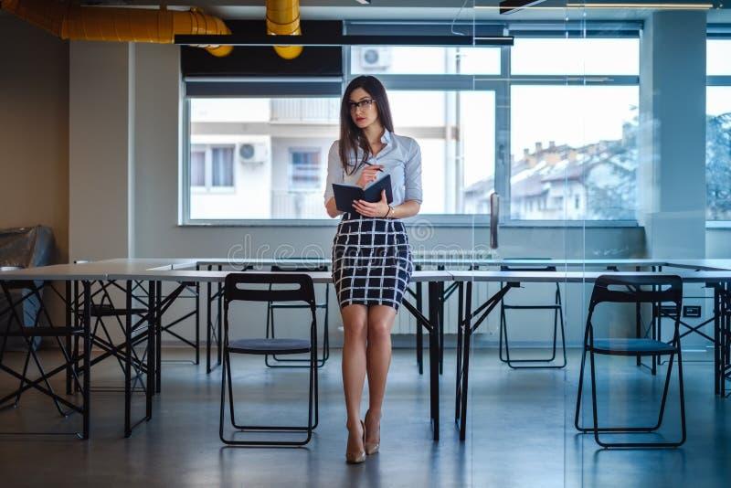 Красивая бизнес-леди сидя на столе офиса и держа примечание стоковое изображение rf