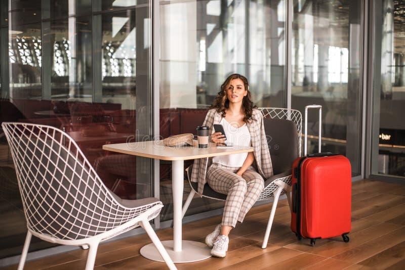 Красивая бизнес-леди со смартфоном ждать ее полет в аэропорт стоковые фото