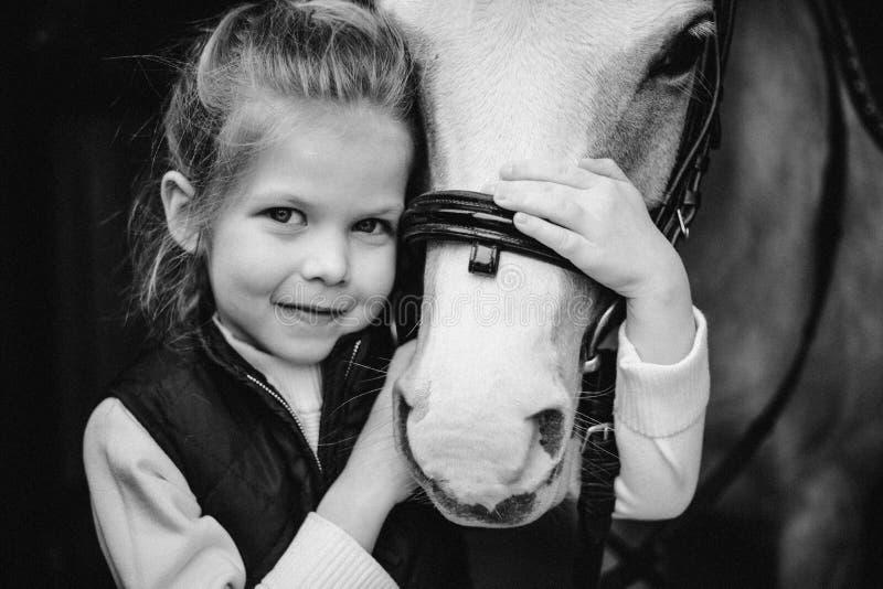 Красивая близкая девушка портрета сидит лошадь beiside на мосте Лес на предпосылке черная белизна черная белизна стоковое фото rf