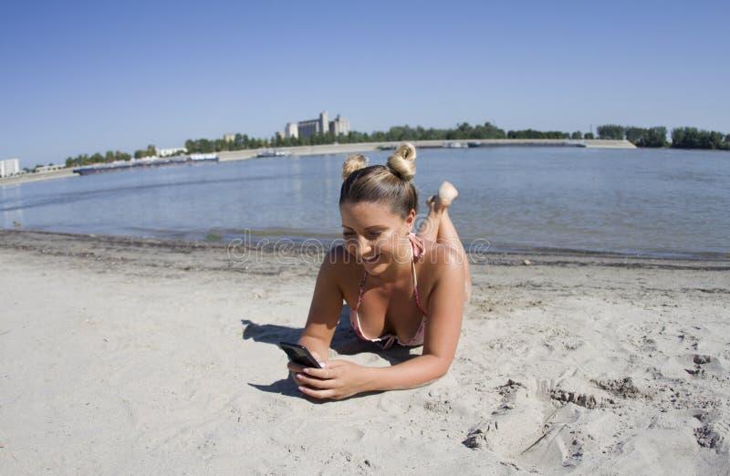 Красивая блондинка Писает сообщения на пляже, песок стоковое фото rf
