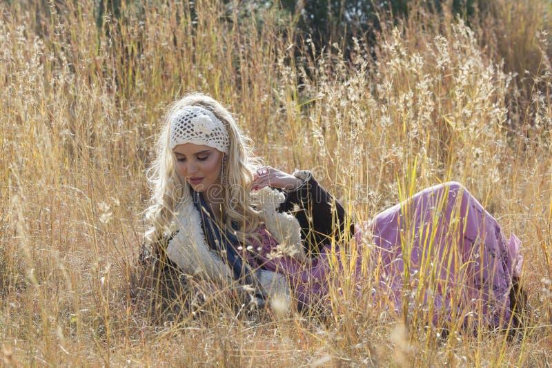 Красивая богемская белокурая женщина лежа в поле травы стоковые фото