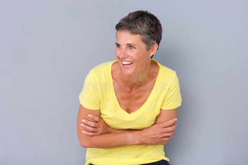 Красивая более старая женщина смеясь над против серой предпосылки стоковая фотография rf