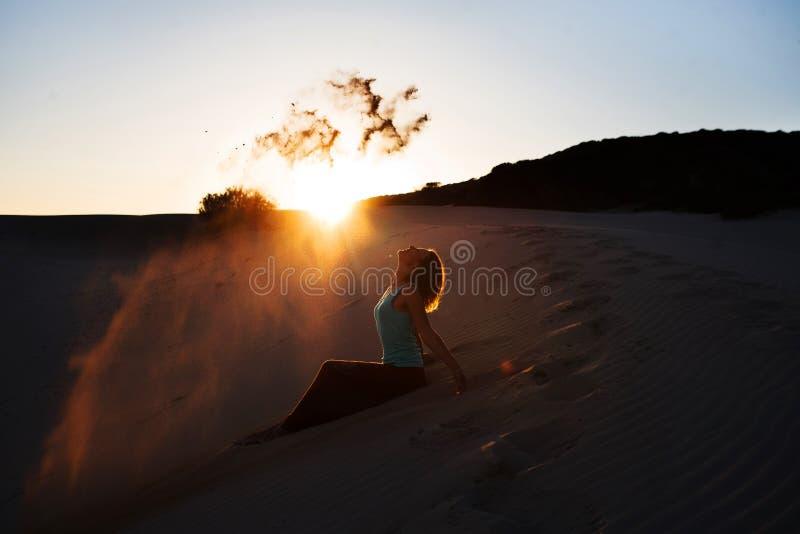 Красивая брошенная женщина песку в дюнах на заходе солнца стоковое фото rf