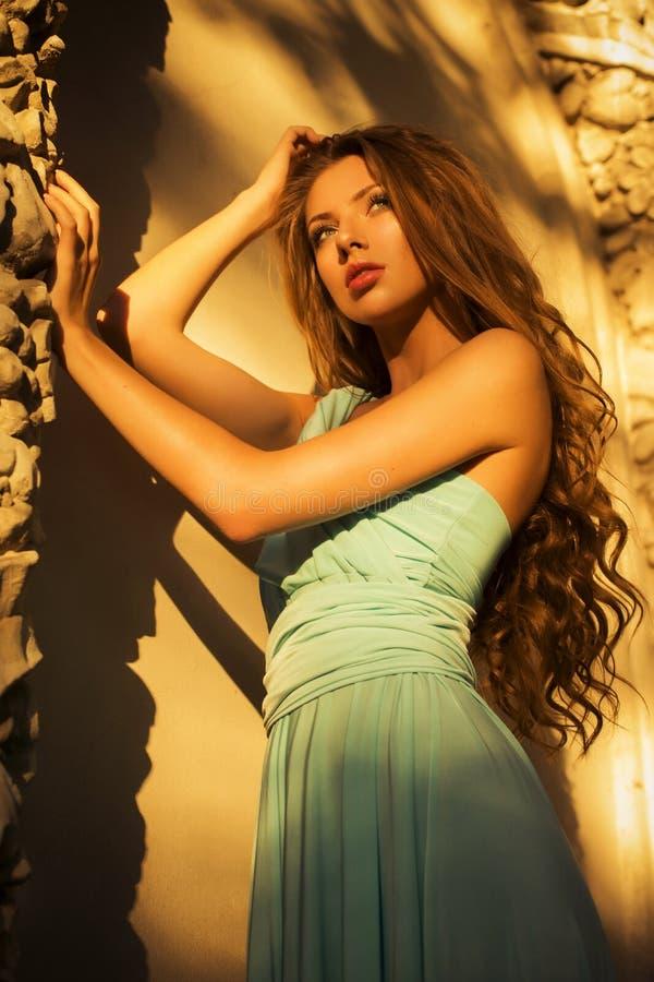 Красивая блондинка с длинным вьющиеся волосы в длинном платье вечера в static outdoors около ретро винтажного здания в заходе сол стоковое изображение