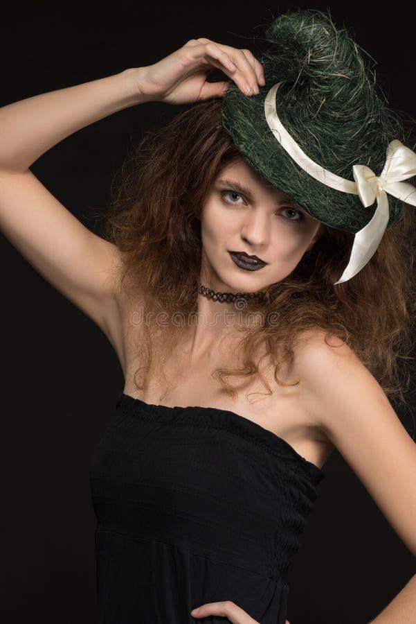 Красивая ведьма женщины в платье с шляпой на голове на черной предпосылке на праздник хеллоуин стоковая фотография rf