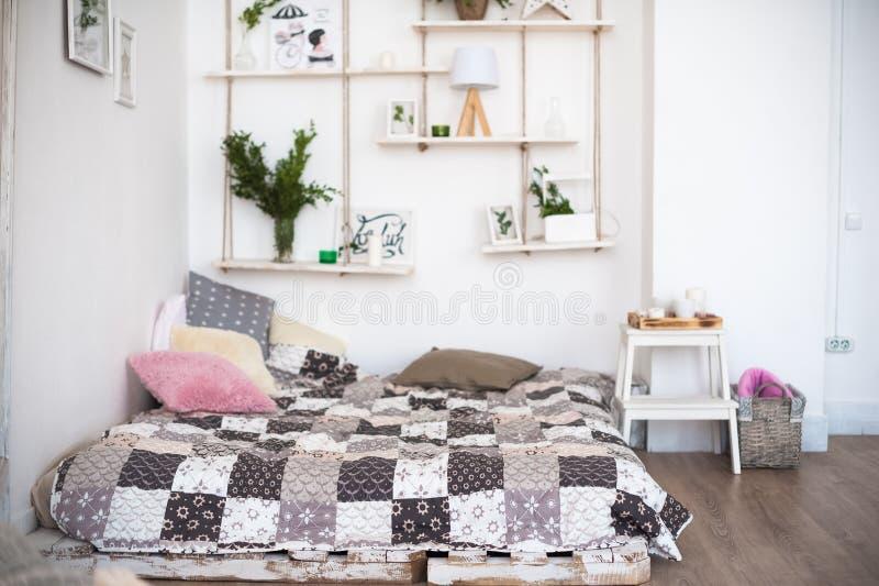 Красивая весна украсила интерьер в белых текстурированных цветах Спальня, кровать на деревянных паллетах стоковые изображения