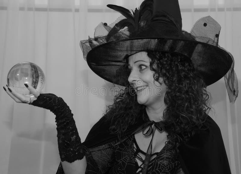 Красивая ведьма брюнет держа хрустальный шар черно-белый стоковые фото