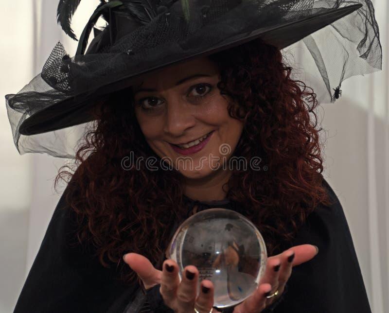 Красивая ведьма брюнет держа хрустальный шар стоковое изображение