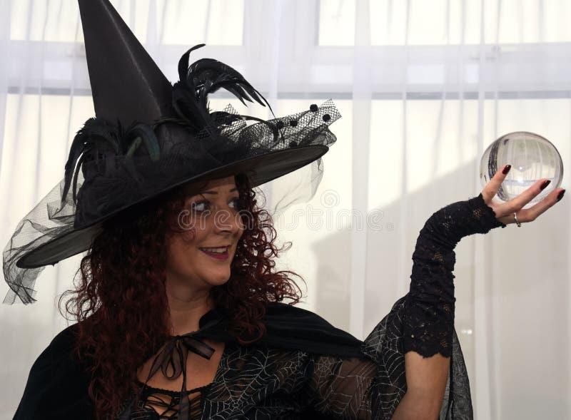Красивая ведьма брюнет держа хрустальный шар стоковое фото rf